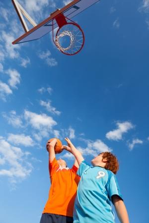 �ngulo de visi�n baja de chicos jugando al baloncesto contra el cielo photo