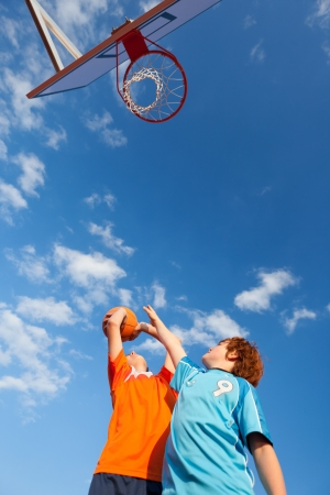 outdoor basketball court: Low angle view of boys playing basketball against sky