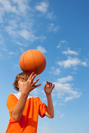 Low angle view of young basketball player spinning ball against sky photo