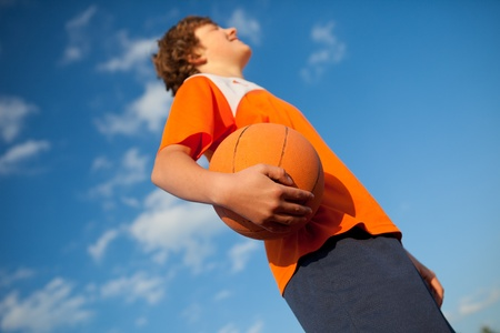 Low angle view of young basketball player holding ball against sky photo