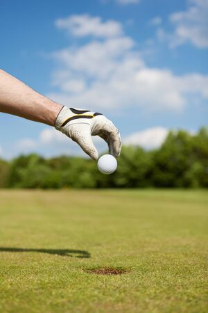 golf glove: golfer putting golf ball by hand in the hole