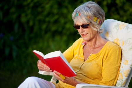 portrait of an elderly lady reading a book with sunglasses photo
