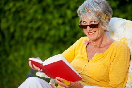 senior woman looking over sunglasses while reading a book photo