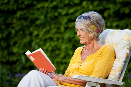 Senior woman reading book while sitting on chair at park photo