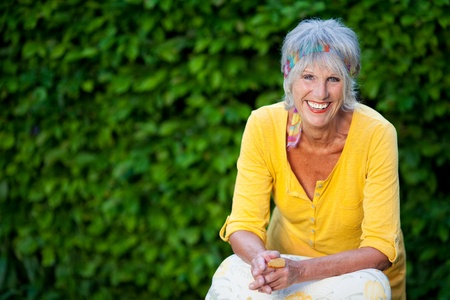 Portrait of happy senior woman sitting against creepers in park photo