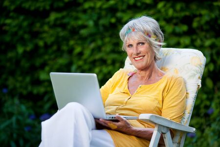 savvy: portrait of a smiling elderly lady using laptop in the garden Stock Photo