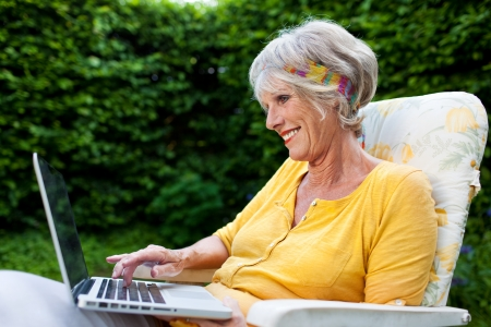 surfing the internet: Senior woman using laptop while sitting on chair at park Stock Photo