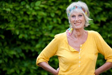 庭に自信を持っている年配の女性の肖像画