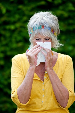 Senior woman blowing nose in tissue paper at park