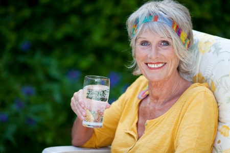 elderly lady sitting in the garden and holding a glass of water