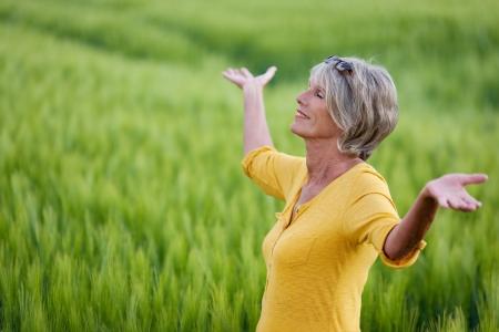 rijpe vrouw met uitgestrekte armen in de natuur Stockfoto