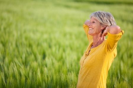 Vista lateral de la mujer mayor feliz con las manos detrás de la cabeza mirando a otro lado en el campo de hierba