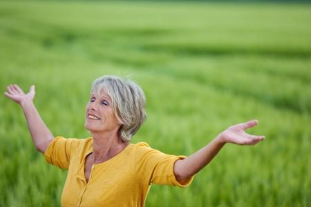 1 senior: Mujer mayor feliz con los brazos extendidos disfrutar de la naturaleza en el campo de hierba