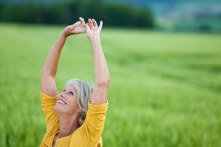 woman mature: Happy senior woman with arms raised looking up while standing on grassy field