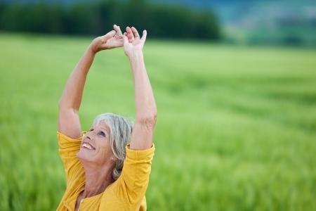 mujeres maduras: Mujer mayor feliz con los brazos en alto mirando hacia arriba mientras está de pie en el campo de hierba
