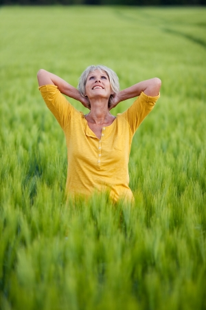 senior lady standing in corn field folding arms behind head