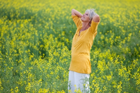 arms raised: Happy relaxed senior woman with hand behind head standing on field
