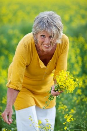 Portrait of happy senior woman plucking flowers on field Stock Photo