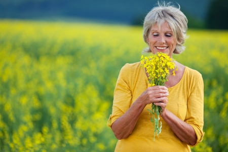 bunch: elderly lady plucking flowers on a field