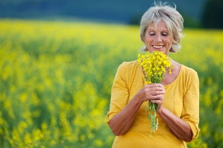 adult rape: elderly lady plucking flowers on a field