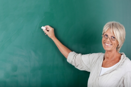 retraining: Senior school teacher giving a smile and writing on the blackboard inside the classroom.