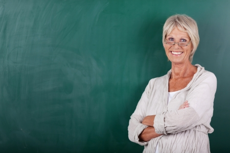 Portrait of happy senior female teacher with arms crossed standing against chalkboard