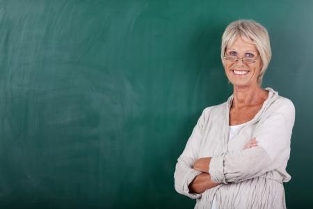 profesor: Retrato de feliz profesora de alto nivel con los brazos cruzados de pie contra la pizarra Foto de archivo