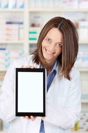 Portrait of happy female pharmacist displaying digital tablet in pharmacy photo