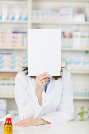 A female pharmacist showing a blank sign inside the drugstore. photo