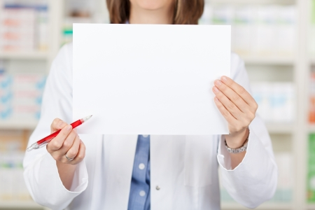 displaying: Midsection of female pharmacist holding pen while displaying blank paper in pharmacy