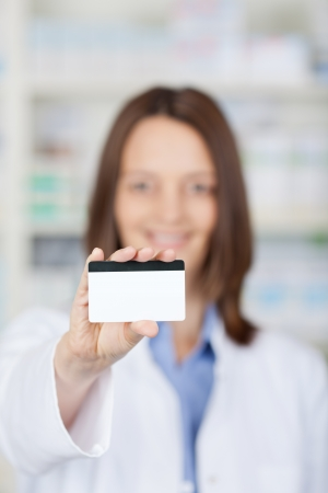 MEMBERSHIP: Closeup of a female pharmacist showing a membership card inside the drugstore. Stock Photo