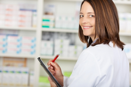 Portrait of female pharmacist looking over shoulder while writing on clipboard in pharmacy Stock Photo - 21260519