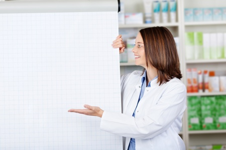 Female pharmacist presenting a flip-chart with a smile. photo