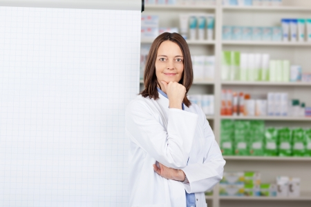 Portrait of confident female pharmacist standing by flipchart in pharmacy photo
