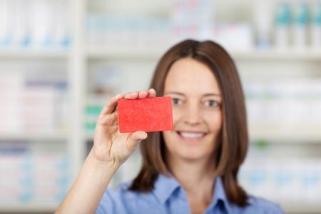 businesscard: Portrait of female pharmacist holding businesscard in pharmacy