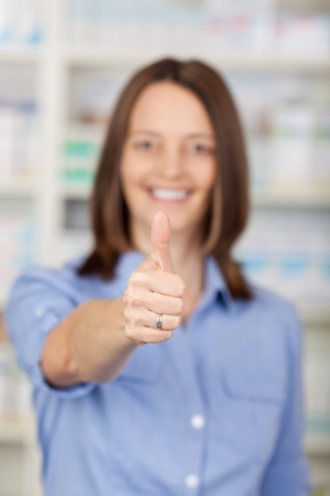 Portrait of female pharmacist showing thumbs up gesture in pharmacy photo
