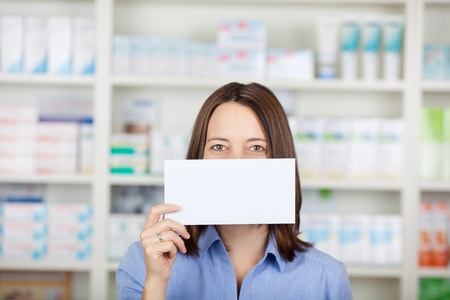 Female customer holding and showing a blank sign standing inside the pharmacy. photo