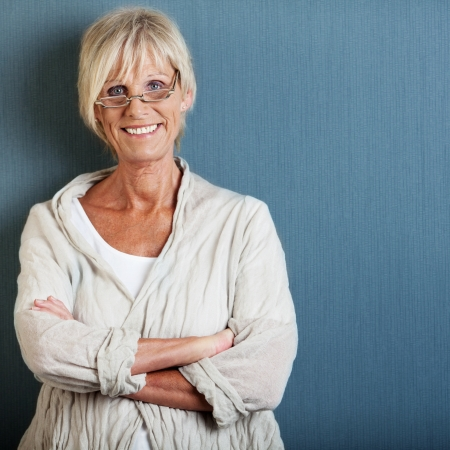 short: Portrait of happy senior woman with arms crossed standing against blue wall Stock Photo