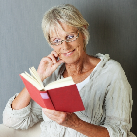 concentrating: Senior woman reading novel while sitting against grey wall