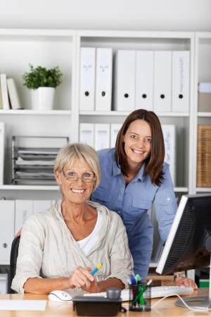 mujeres trabajando: Un anciano y joven mujer sonriente posando dentro de la oficina.