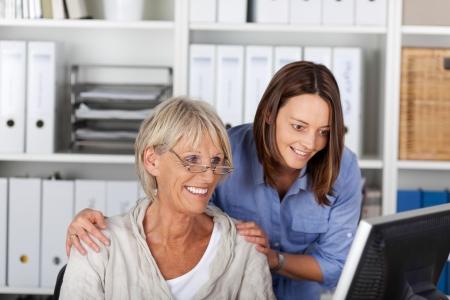 przewidywanie: Sukces zespołu w biurze, składający się z osób starszych i młoda kobieta stojąca ramię w ramię studia pulpit monitora z uśmiechem na oczekiwaniu