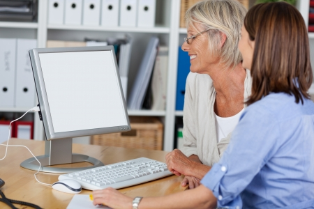 Females of different generations looking at the computer, working together in the office. Stock Photo