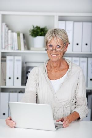 Sorridente senior donna con il computer portatile sulla scrivania