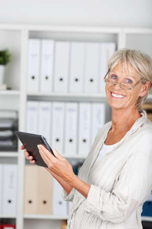 Good looking older woman holding a tablet photo