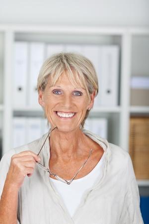 Smiling senior woman holding her glasses portrait photo