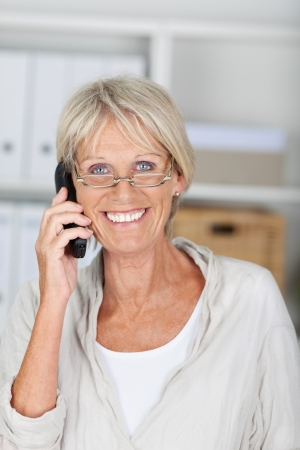 Portrait of happy senior businesswoman conversing on cordless phone at office photo
