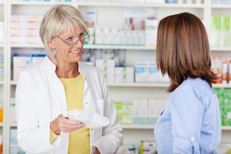 Senior vrouwelijke apotheker geven van voorgeschreven medicijnen aan klanten in de farmacie