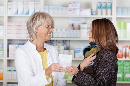 advice: Pharmacist giving medication to a female in the pharmacy