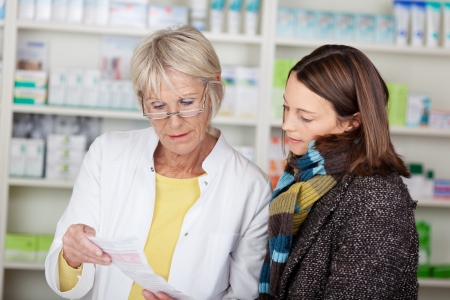 serious woman: Pharmacist explaining the prescription to the female customer