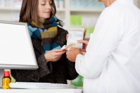 Midsection of pharmacist receiving money from female customer for medicines at pharmacy photo
